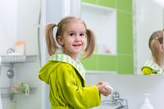 Cute child little girl with ponytail in green bathrobe washing her hands in bathroom royalty free stock images