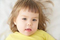 Cute little girl portrait face lying on white blanket Stock Photos