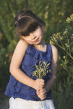 Cute little girl posig at sunset with flowers Royalty Free Stock Photography