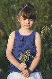 Cute little girl posig at sunset with flowers Royalty Free Stock Photo