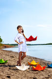 Cute little girl posing with colorful paper boats Stock Image