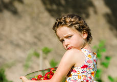 Cute little girl posing with fresh red strawberry in the sunny g Royalty Free Stock Photos