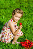 Cute little girl posing with fresh red strawberry in the sunny g Royalty Free Stock Photo