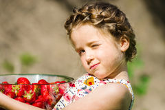Cute little girl posing with fresh red strawberry in the sunny g Stock Photo