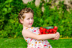Cute little girl posing with fresh red strawberry in the sunny g Stock Photos