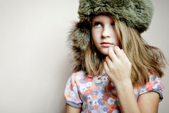 Cute little girl posing in a fur hat. Royalty Free Stock Photos
