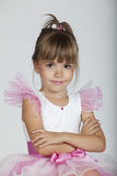 Cute little girl posing in her tutu. Portrait of a cute ballerina with crossed arms, studio image Stock Photo