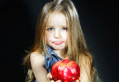 Cute little girl posing with red pomegranate Royalty Free Stock Image