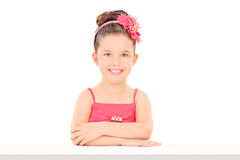 Cute little girl posing seated at a table Royalty Free Stock Photos