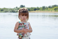 Cute little girl posing with soap bubbles at lake Stock Image