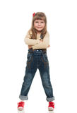 Cute little girl posing in studio. Cute little girl wearing jeans overall posing in studio and smiling on white background Royalty Free Stock Images