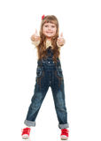 Cute little girl posing in studio. Cute little girl wearing jeans overall posing in studio howing ok sign and smiling on white background Royalty Free Stock Images