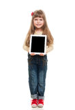 Cute little girl posing in studio. Cute little girl wearing jeans overall posing in studio with white tablet gadget and smiling on white background Stock Image
