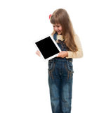 Cute little girl posing in studio. Cute little girl wearing jeans overall posing in studio with white tablet gadget and smiling on white background Royalty Free Stock Photography