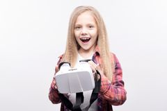 Cute little girl posing with a VR headset. New toy. Upbeat adorable little girl holding a VR headset and smiling brightly while posing for the camera, standing Royalty Free Stock Photography