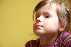 Cute little girl potrait, yellow back, natural Royalty Free Stock Photo