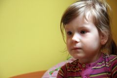 Cute little girl potrait, yellow back, natural Stock Images