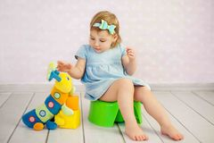 Cute little girl potty trainting with a toy at house. Lovely baby boy with toys and waffle sitting on potty Royalty Free Stock Photography