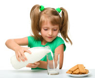 Cute little girl is pouring milk in glass Royalty Free Stock Images