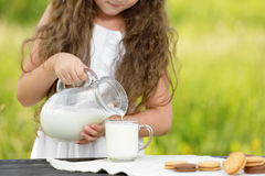Cute little girl pouring milk in glass having breakfast outdoor summer Royalty Free Stock Images