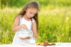 Cute little girl pouring milk in glass having breakfast outdoor summer Royalty Free Stock Photo