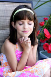 Cute little girl in prayer. A very cute little girl with eyes closed and dark hair sitting by pink flowers in prayer. Shallow depth of field Stock Photography