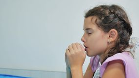 Cute little girl praying at home. little girl prays in the evening before bedtime bed. little girl and religion concept stock video footage