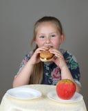 Cute little girl preferred hamburger instead of apple royalty free stock photo