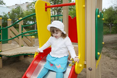 Cute little girl prepares for rolling at slide Royalty Free Stock Photography