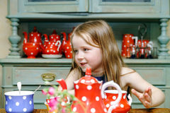 Cute little girl preparing tea in teapot. On the kitchen, childhood concept royalty free stock photography