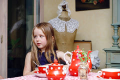 Cute little girl preparing tea in teapot. On the kitchen, childhood concept stock photo