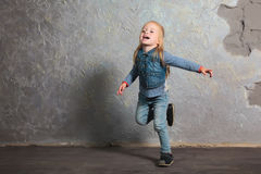 Cute little girl pretending to fly. Posing and playing. Cute toddler girl posing joyfully to camera. Pretending to fly. Vintage background. Happy childhood Stock Image