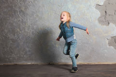 Cute little girl pretending to fly. Posing and playing. Cute toddler girl posing joyfully to camera. Pretending to fly. Vintage background. Happy childhood Royalty Free Stock Images