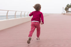 Cute little girl on the promenade by the sea Stock Images