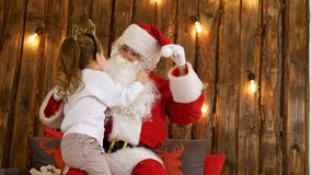 Cute little girl pulling Santa`s beard to check if it`s real sitting on his lap Royalty Free Stock Photo