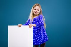 Cute little girl in purple dress holds empty poster Royalty Free Stock Images