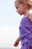 Cute little girl in purple dress playing on the sea sand Royalty Free Stock Images