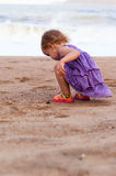Cute little girl in purple dress playing on the sea sand Royalty Free Stock Image
