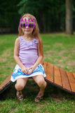 Cute little girl in purple Happy Birthday glasses Royalty Free Stock Image