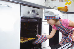 Cute little girl put cookies in stove Stock Images