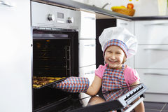 Cute little girl put cookies in stove Stock Image