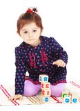 Cute little girl puts cubes sitting on the carpet Royalty Free Stock Image