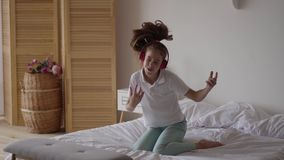 Funny cute little girl putting on headphones and trying to dance and falling on the bed. Young music lover having fun stock video