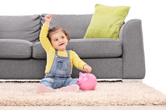 Cute little girl putting money into a piggybank Stock Photo
