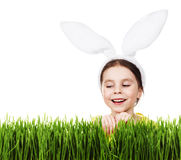 Cute little girl in a rabbit costume peeking out of the grass Royalty Free Stock Photography