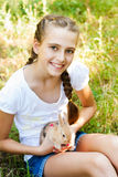 Cute little girl with a rabbit in the garden. Stock Images
