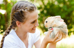 Cute little girl with a rabbit in the garden. Royalty Free Stock Photography