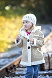 Cute little girl on railroad tracks in coat Stock Image