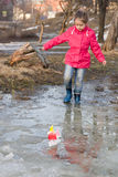 Cute little girl in rain boots playing with colorful ships in the spring creek walking in water Stock Image