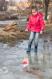 Cute little girl in rain boots playing with handmade colorful ships in the spring creek standing in water Royalty Free Stock Images